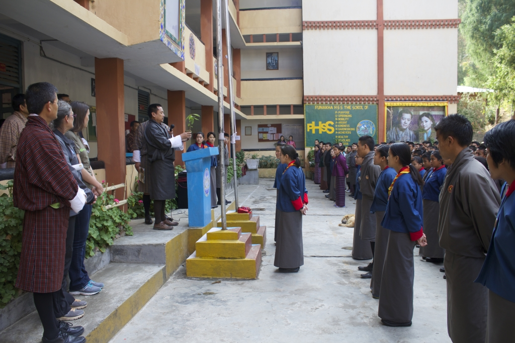 The Minister of Forests demonstrates how to plant a tree to the students.